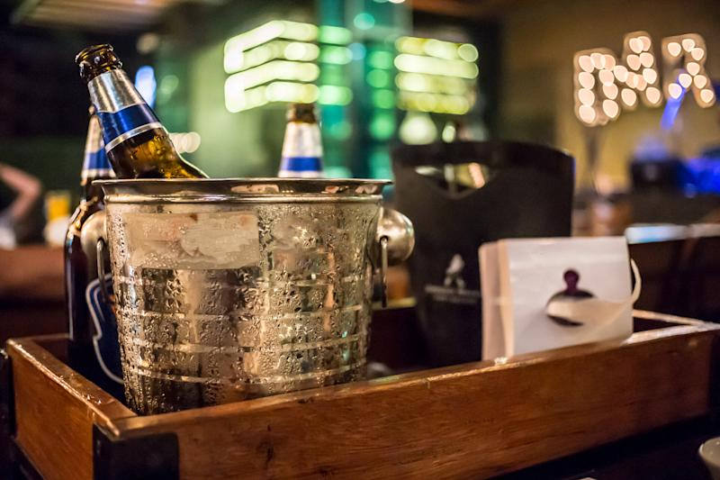 ice bucket of cold bottles beer In the bar and restaurant setting .