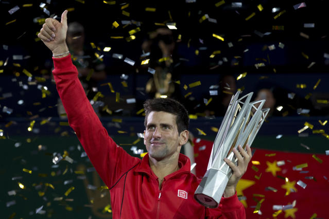 Serbia's Novak Djokovic celebrates with his trophy after defeating Argentina's Juan Martin del Potro in their final match of the Shanghai Masters tennis tournament at the Qizhong Forest Sports City Tennis Center in Shanghai, China, Sunday, Oct. 13, 2013. Djokovic won 6-1, 3-6, 7-6 (3). (AP Photo/Ng Han Guan)