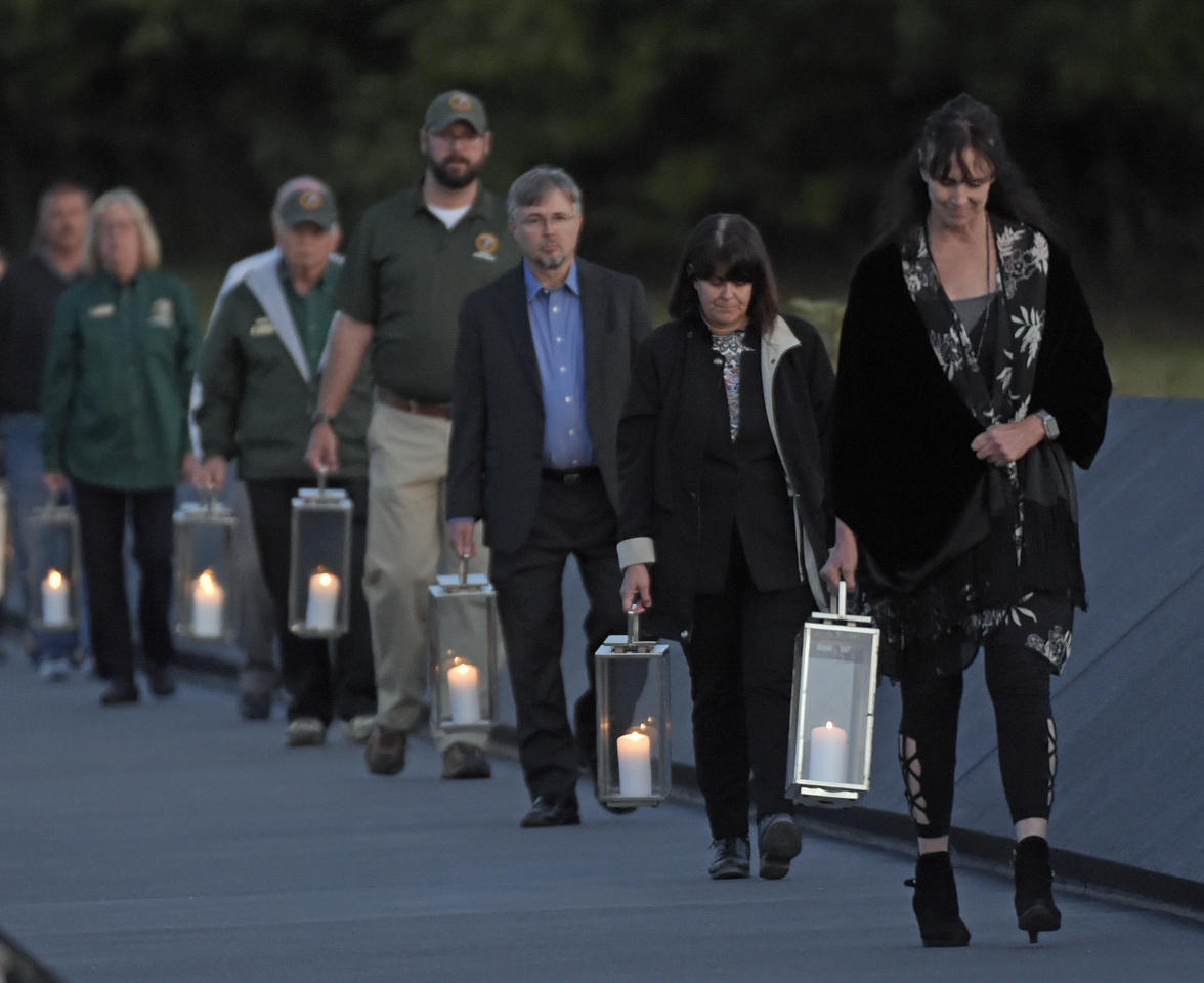 Candles in memory of the passengers and crew of United Flight 93, are carried to the Wall of Names at the Flight 93 National Memorial in Shanksville, Pa., Saturday, Sept. 10, 2017. (AP Photo/Fred Vuich)