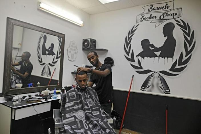 Israeli Ethiopian Jewish hairdresser Baruch works at his barbershop in the southern Israeli city of Ashkelon. Israel's 140,000-strong Ethiopian-Israeli community could prove pivotal in the Jewish state's tight March 2 election. (AFP Photo/MENAHEM KAHANA)