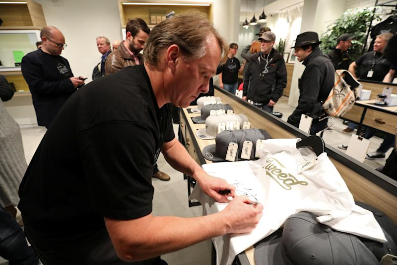Canopy Growth CEO Bruce Linton autographs a t-shirt after legal recreational marijuana went on sale at a Tweed retail store in St John's, Newfoundland and Labrador, Canada October 17, 2018. REUTERS/Chris Wattie