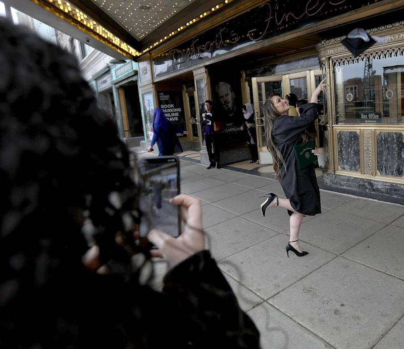 Intisar Fawaz, 22 has fun with her graduation cap as her sister Naveen Fawaz photographs her with her iPhone in front of the Fox Theatre in downtown Detroit on Friday, May 3, 2019. Fawaz had just graduated from Wayne State University with a Bachelors of Arts in Biology.