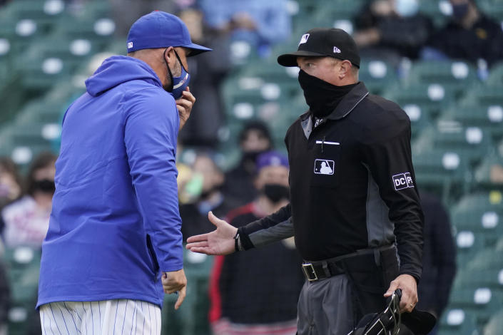 Chicago Cubs manager David Ross, left, argues with umpire Cory Blaser during the ninth inning of a baseball game against the Milwaukee Brewers in Chicago, Saturday, April 24, 2021. (AP Photo/Nam Y. Huh)