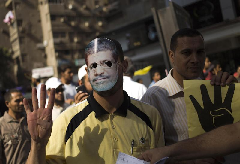 Supporters of Egypt's ousted President Mohammed Morsi, one wearing a mask with the former leader's likeness and holds placard showing an open palm with four raised fingers, which has become a symbol of the Rabaah al-Adawiya mosque, where Morsi supporters had held a sit-in for weeks that was violently dispersed in August during a protest in Cairo, Egypt, Friday, Oct. 4, 2013. (AP Photo/Hassan Ammar)