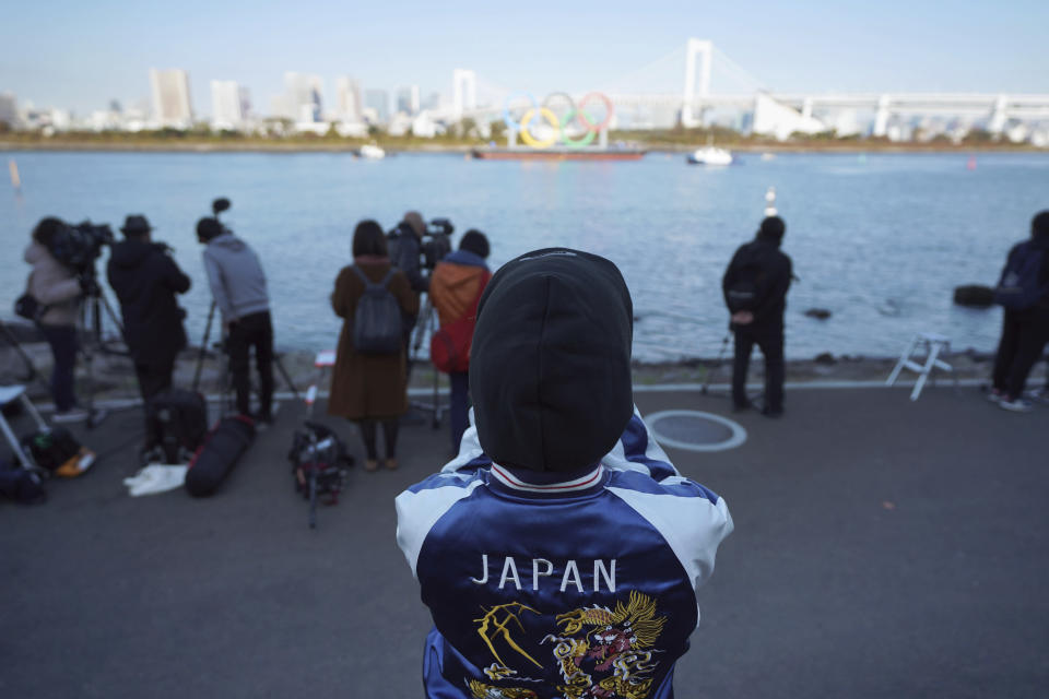 A woman watches at the Olympic Symbol being transported on a barge in the Odaiba section Tuesday, Dec. 1, 2020, in Tokyo. The five Olympic rings are back in Tokyo Bay. They were removed for maintenance four months ago shortly after the Tokyo Olympics were postponed until next year because of the COVID-19 pandemic. (AP Photo/Eugene Hoshiko)