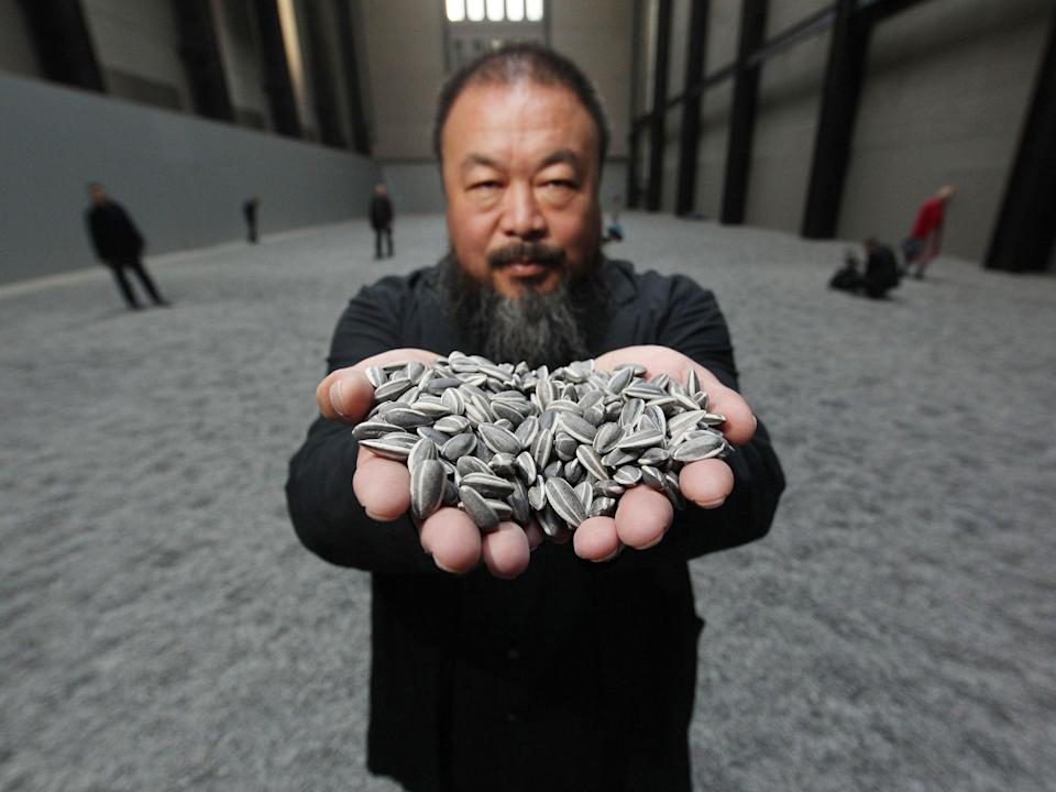 Ai Weiwei holds some seeds from his Unilever installation Sunflower Seeds at Tate Modern, October 2010Getty