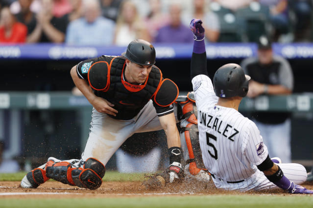 Miami Marlins catcher J.T. Realmuto, left, applies a late tag on Colorado Rockies' Carlos Gonzalez who scores on a bunt put down by Jon Gray in the fourth inning of a baseball game Friday, June 22, 2018, in Denver. (AP Photo/David Zalubowski)