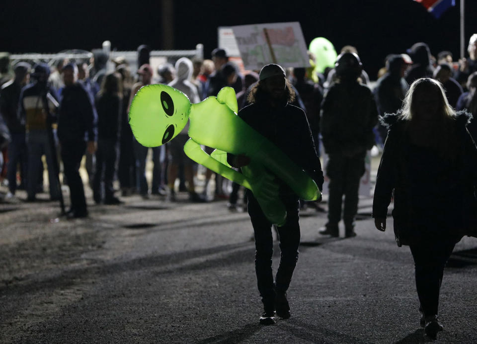 """A mans holds an inflatable alien at an entrance to the Nevada Test and Training Range near Area 51 Friday, Sept. 20, 2019, near Rachel, Nev. People gathered at the gate inspired by the """"Storm Area 51"""" internet hoax. (AP Photo/John Locher)"""