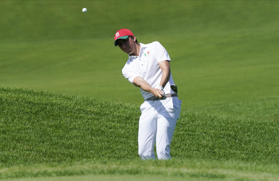 Carlos Ortiz of Mexico chips onto the 12th green during the third round of the men's golf event at the 2020 Summer Olympics on Saturday, July 31, 2021, in Kawagoe, Japan. (AP Photo/Matt York)