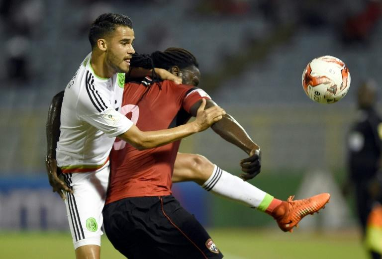 Mexico's Diego Reyes (L) fights for the ball with Trinidad & Tobago's Kenwyne Jones during their Russia 2018 World Cup qualifier match, in Port of Spain, on March 28, 2017