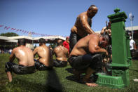 An exhausted wrestler tries to cool off after he competed on the second day of the 660th instalment of the annual Historic Kirkpinar Oil Wrestling championship, in Edirne, northwestern Turkey, Saturday, July 10, 2021.Thousands of Turkish wrestling fans flocked to the country's Greek border province to watch the championship of the sport that dates to the 14th century, after last year's contest was cancelled due to the coronavirus pandemic. The festival, one of the world's oldest wrestling events, was listed as an intangible cultural heritage event by UNESCO in 2010. (AP Photo/Emrah Gurel)