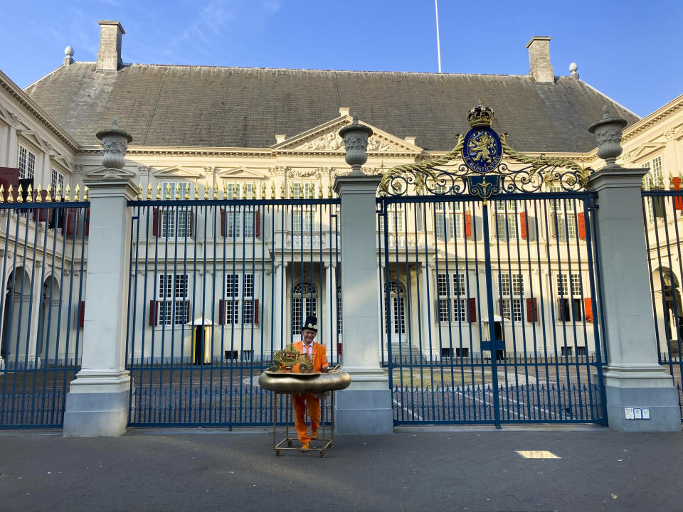 """Resplendent in orange suit, tie and shoes and a black hat with gold bow and protected by a homemade """"corona bumper"""" decorated with a model carriage, Johan Vlemmix, center, stands in front of Royal Palace Noordeinde, in The Hague, Netherlands, Tuesday, Sept. 15, 2020. Vlemmix drove three hours to get to The Hague, as he has done every budget day for more than 20 years, to watch King Willem-Alexander and Queen Maxima appear on the palace balcony, rear. The balcony appearance of the king and queen has been cancelled due to COVID-19 related measures. """"It's surreal,"""" he said. """"You see the red carpet has been rolled out, the king has arrived and there's nobody here. I've never experienced this. (AP Photo/Mike Corder)"""
