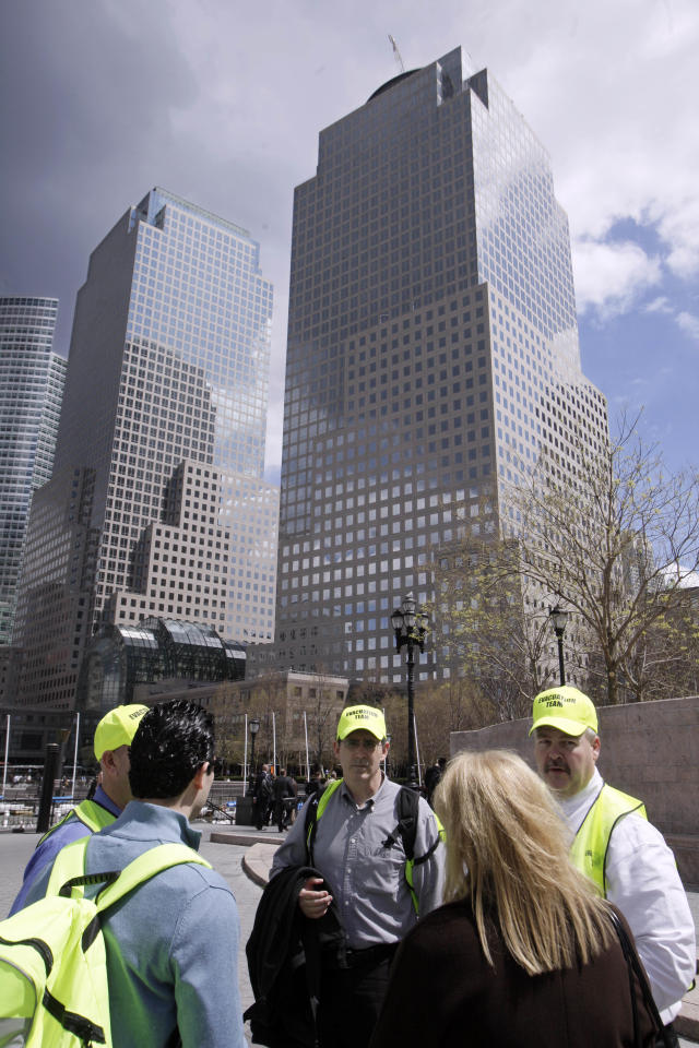 A evacuation team confers outside 2 World Financial Center, right, in New York,  Thursday, April 12, 2012. Authorities say an evacuation was ordered as a precaution after a security guard reported a package that seemed suspicious. The One World Trade Center building under construction, inside Ground Zero, is visible at center. (AP Photo/Richard Drew)