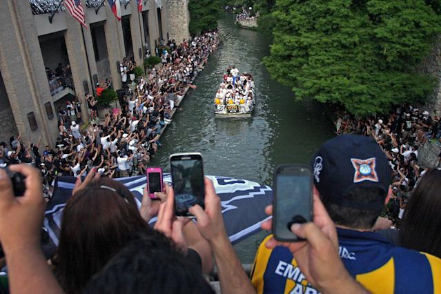 San Antonio fans record the Riverwalk boats carrying Spurs' players during the Spurs' parade and celebration of their 5th NBA Championship in San Antonio, Texas, Weds., June 18, 2014