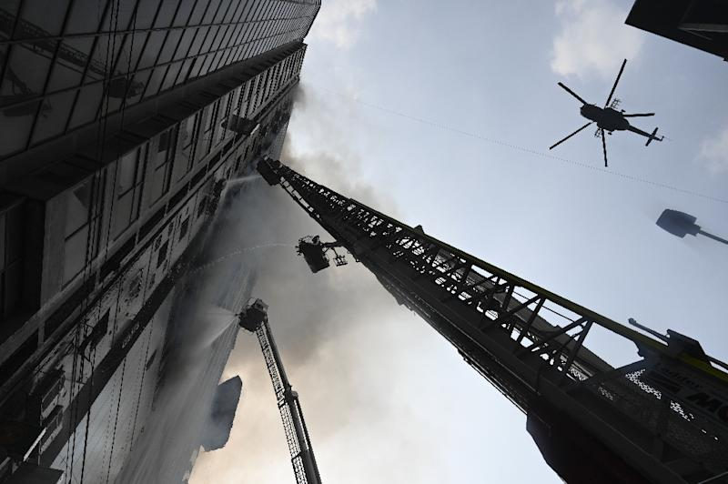 Helicopters were called in to tackle the blaze in the 22-storey building in Dhaka's business district (AFP Photo/MUNIR UZ ZAMAN)