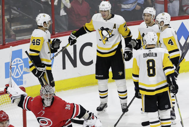 Carolina Hurricanes goalie Cam Ward holds his broken stick as Pittsburgh Penguins' Evgeni Malkin is congratulated on his goal by teammates Zach Aston-Reese (46), Brian Dumoulin (8), Justin Schultz (4) and Patric Hornqvist, of Sweden, during the third period of an NHL hockey game in Raleigh, N.C., Friday, Feb. 23, 2018. Pittsburgh won 6-1. (AP Photo/Gerry Broome)