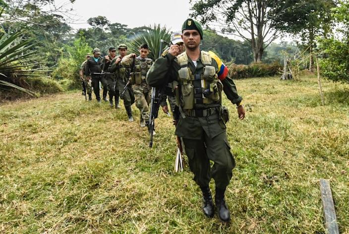Revolutionary Armed Forces of Colombia members walk towards a camp in the Magdalena Medio region, Antioquia department, Colombia (AFP Photo/Luis Acosta)