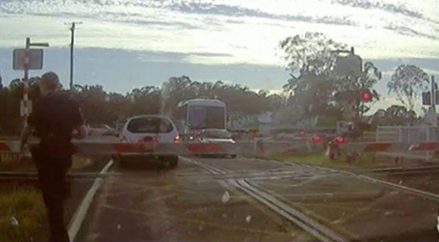 An officer can be seen walking from his car to where a Queensland motorist became stuck between two boom gates at a railway level crossing. Picture: Queensland Police