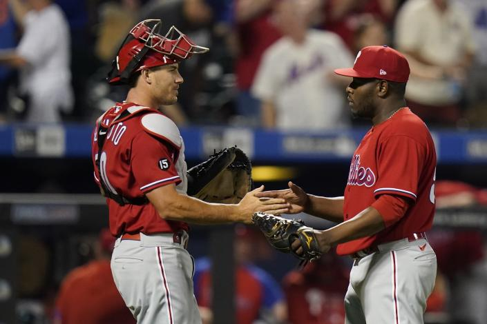 Philadelphia Phillies' J.T. Realmuto, left, celebrates with relief pitcher Hector Neris, right, after the second baseball game of a doubleheader against the New York Mets Friday, June 25, 2021, in New York. (AP Photo/Frank Franklin II)