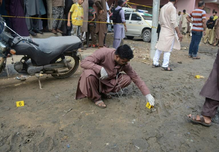 A Pakistani investigator inspects the scene of the attack on  opposition politician Khawaja Izharul Hassan in Karachi in September