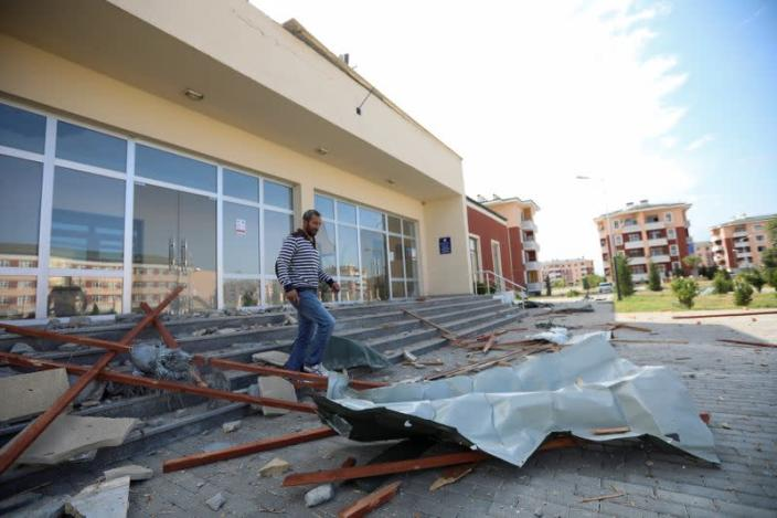 A man walks through the debris from a building that was allegedly damaged by recent shelling during the fighting over the breakaway region of Nagorno-Karabakh, in Shikharkh