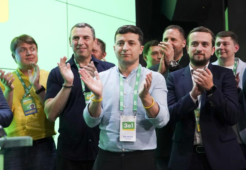 Ukrainian President Volodymyr Zelenskiy, center, applauds with his team at his party's headquarters after a parliamentary election in Kiev, Ukraine, Sunday, July 21, 2019. Zelenskiy's party took the largest share of votes in the country's snap parliamentary election, an exit poll showed Sunday. (AP Photo/Evgeniy Maloletka)