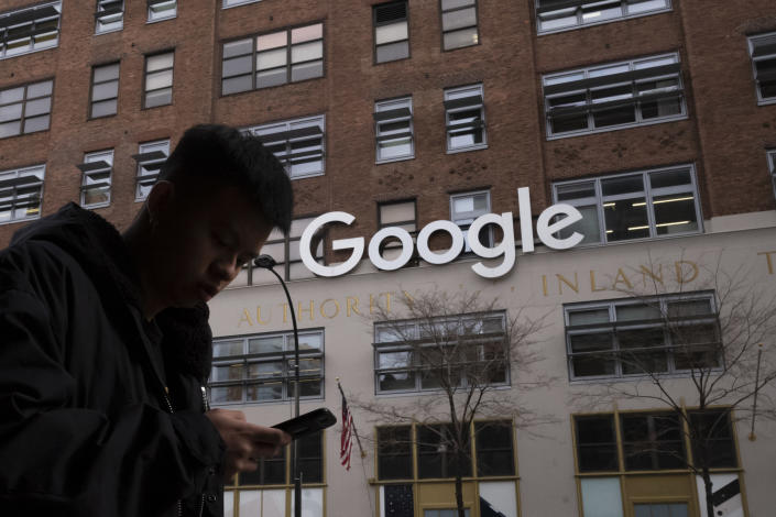 FILE - In this Dec. 17, 2018, file photo a man using a mobile phone walks past Google offices in New York. Australia's laws forcing Google and Facebook to pay for news are ready to take effect, though the laws' architect said it will take time for the digital giants to strike media deals. The Parliament on Thursday, Feb . 25, 2021, passed amendments to the so-called News Media Bargaining Code agreed between Treasurer Josh Frydenberg and Facebook chief executive Mark Zuckerberg on Tuesday. (AP Photo/Mark Lennihan, File)