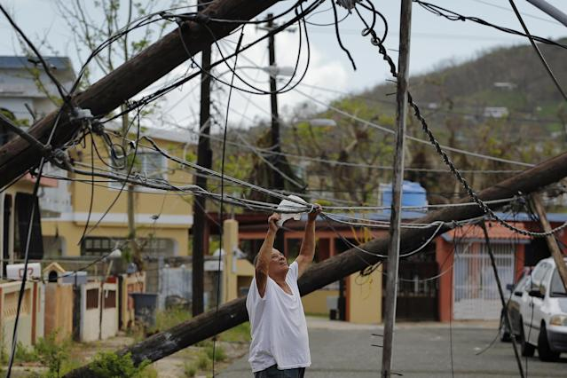 <p>A resident uses a plastic bag to move downed power cables so he can drive underneath them in a neighborhood following Hurricane Maria in Ceiba, Puerto Rico, Oct. 4, 2017. (Photo: Lucas Jackson/Reuters) </p>