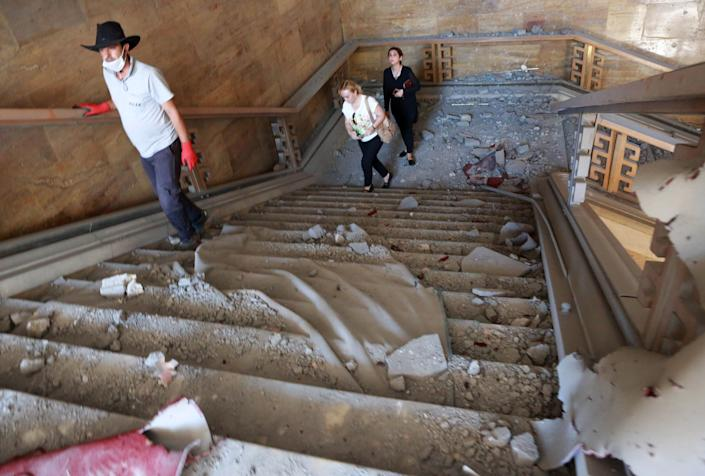 People walk through rubble afterthe Grand National Assembly of Turkey was bombed by rebel jets.