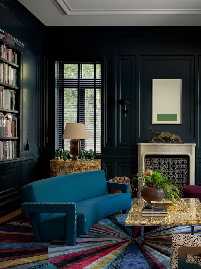 The library ensemble includes a Gerrit Rietveld sofa by Cassina, an Yves Klein table, a Marie Suri fire screen, a Piero Fornasetti cabinet, and a custom Tai Ping carpet by The Archers. The painting is by Karl Benjamin.