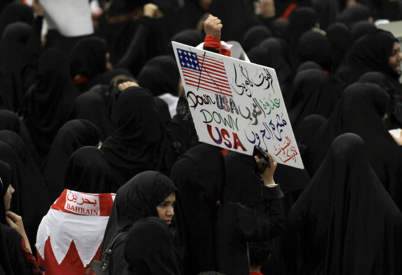 """In this photo taken May 18, 2012, Bahraini anti-government protesters participating in mass march along a northern highway outside Manama, Bahrain, carry a sign reading in Arabic, """"Death to America, the enemy of the nations and the creator of wars. Death to America."""" During one of the nightly clashes with Bahrain's security forces, a new chant broke out among opposition protesters: """"The U.S. is the big devil."""" A few days later, pro-government marchers also waved their fists against Washington. Both sides in the Bahrain meltdown are finding a shared target in the United States. (AP Photo/Hasan Jamali)"""
