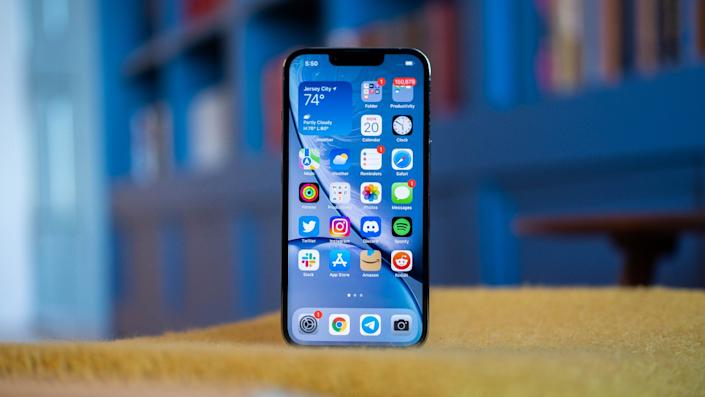 An iPhone 13 Pro standing on a fabric surface with its screen facing the camera.