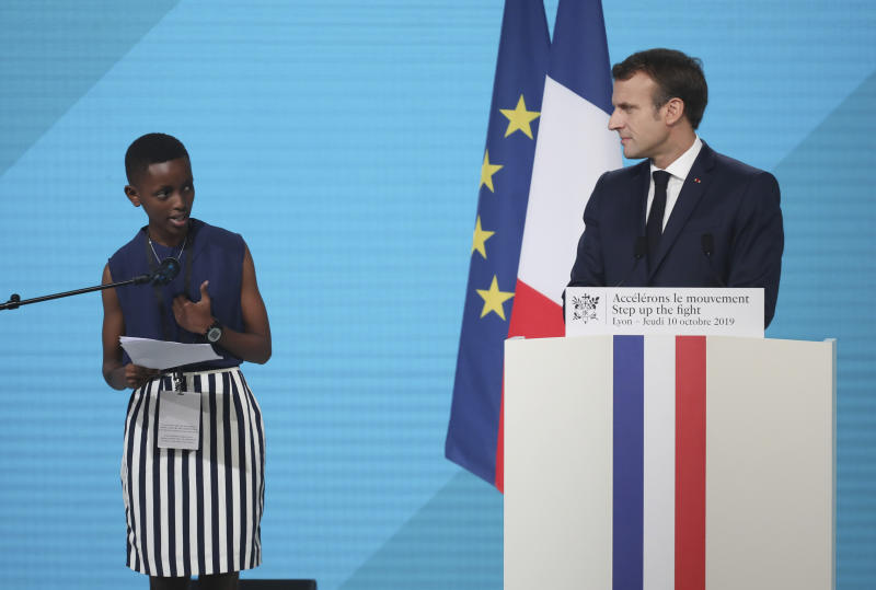 "France's President Emmanuel Macron, right, listening to the goodwill ambassador of the ONG ""Grandir Ensemble"" Amanda Dushime at the Lyon's congress hall, central France, Thursday, Oct. 10, 2019, during the meeting of international lawmakers, health leaders and people affected by HIV, Tuberculosis and malaria. Lyon is hosting the two day Global Fund event aimed at raising money to help in the global fight against the epidemics. (AP Photo/Laurent Cipriani)"