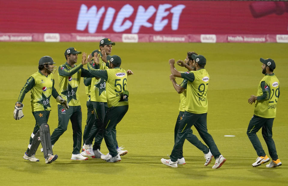 FILE - In this Tuesday Sept. 1, 2020, file photo, Pakistan players celebrate the dismissal of England's Dawid Malan during the third Twenty20 cricket match between England and Pakistan, at Old Trafford in Manchester, England. Six members of the Pakistan cricket squad in New Zealand have tested positive, Thursday Nov. 26, 2020, for COVID-19 and have been moved from managed isolation into quarantine. (AP Photo/Jon Super, Pool,File)