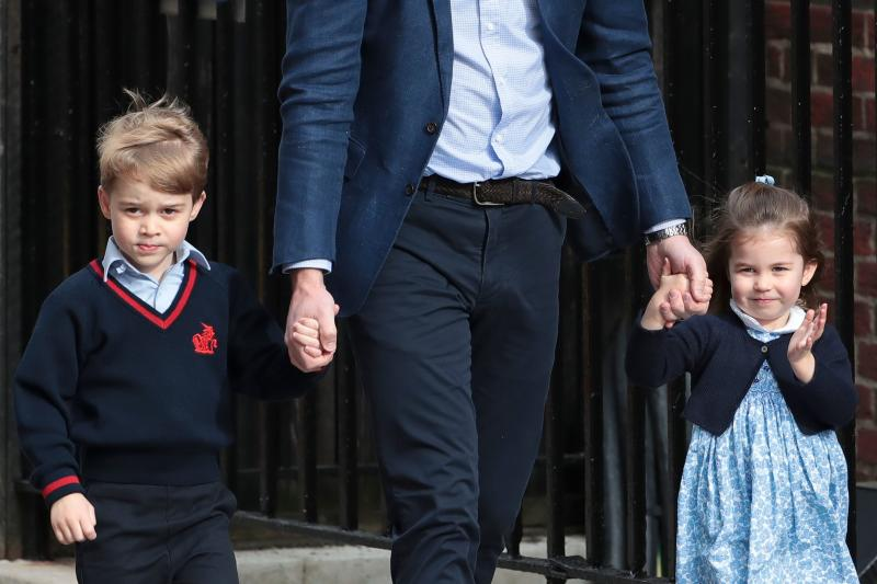 "TOPSHOT - Princess Charlotte of Cambridge (R) waves at the media as she is led in with her brother Prince George of Cambridge (L) by their father Britain's Prince William, Duke of Cambridge, (C) at the Lindo Wing of St Mary's Hospital in central London, on April 23, 2018, to visit Catherine, Duchess of Cambridge, and their new-born brother, the Duke and Duchesses third child. - Kate, the wife of Britain's Prince William, has given birth to a baby son, Kensington Palace announced Monday. ""Her Royal Highness The Duchess of Cambridge was safely delivered of a son at 11:01 (1001 GMT),"" the palace said in a statement. The baby boy weighs eight pounds and seven ounces (3.8 kilogrammes). (Photo by Daniel LEAL-OLIVAS / AFP) (Photo credit should read DANIEL LEAL-OLIVAS/AFP via Getty Images)"