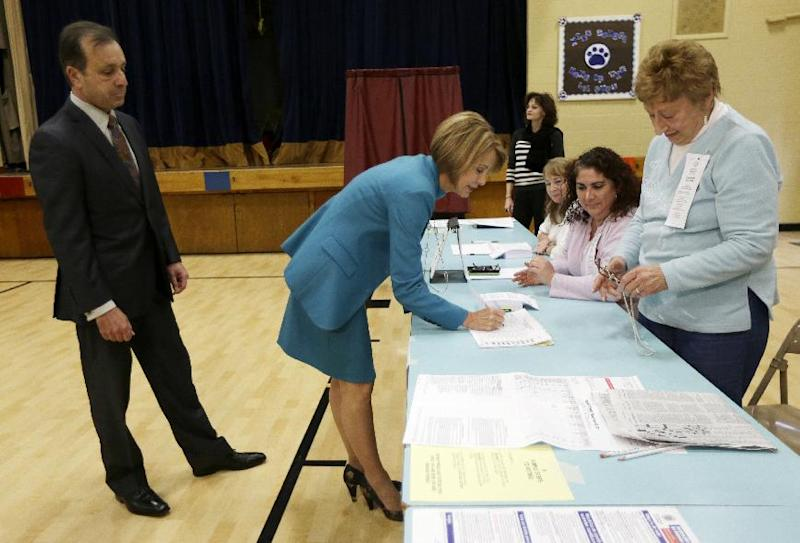 New Jersey Democratic gubernatorial candidate Barbara Buono, center, checks in before casting her vote with her husband Martin Gizzi, left, Tuesday, Nov. 5, 2013, in Metuchen, N.J. Buono is challenging Republican Gov. Chris Christie, who is running for re-election. (AP Photo/Julio Cortez)
