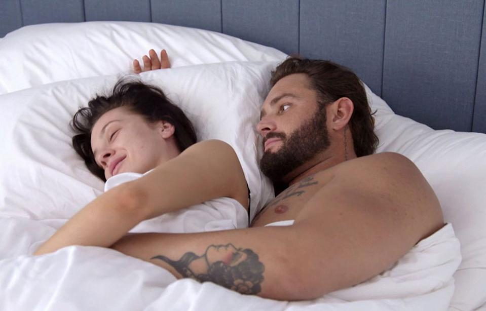 A screenshot of Married At First Sight contestants Ines Basic and Sam Ball in bed together in season six