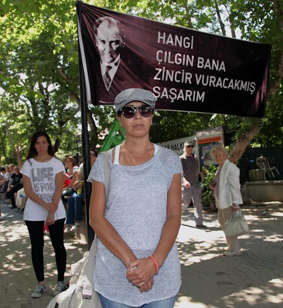 "Turks stand in a silent protest in Kugulu Park in Ankara, Turkey, Wednesday, June 19, 2013. After weeks of sometimes-violent confrontation with police, Turkish protesters have found a new form of resistance: standing still and silent. The banner with an image of Turkey's founder Kemal Ataturk reads: "" Which crazy person thinks they can put me in chains."" (AP Photo/Burhan Ozbilici)"