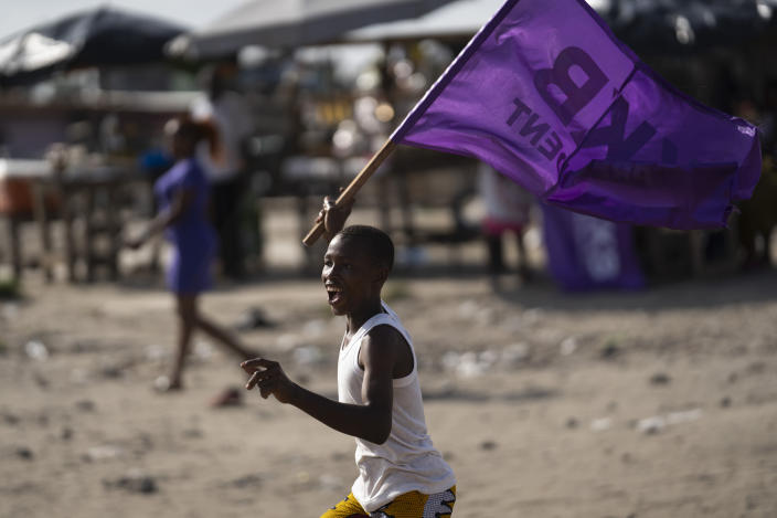 A boy runs as he waves a flag in support of the presidential candidate Kouadio Konan Bertin, during the final campaign rally in Abidjan, Ivory Coast, Thursday, Oct. 29, 2020. Bertin, known as KKB, has presented his candidacy as an independent candidate for the upcoming Oct. 31 election, and said he would not join the boycott proposed by two main opponents of Ivory Coast President Alassane Ouattara. (AP Photo/Leo Correa)