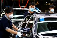 FILE PHOTO: Employees wearing face masks work at a plant of Daimler-BAIC joint venture's Beijing Benz Automotive Co during a government organised tour of the facility following the outbreak of the coronavirus disease (COVID-19), in Beijing