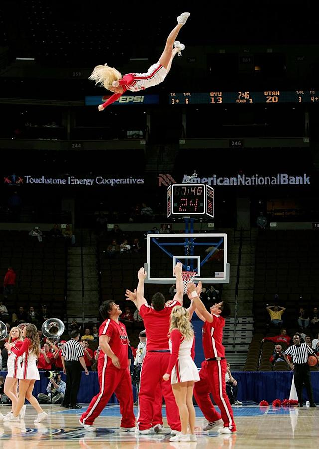 A cheerleader for the Utah Runnin' Utes is launched into the air by members of her squad as the Utes face the Brigham Young University Cougars during the Mountain West Conference Basketball Tournament March 9, 2006 at the Pepsi Center in Denver, Colorado. (Photo by Doug Pensinger/Getty Images)