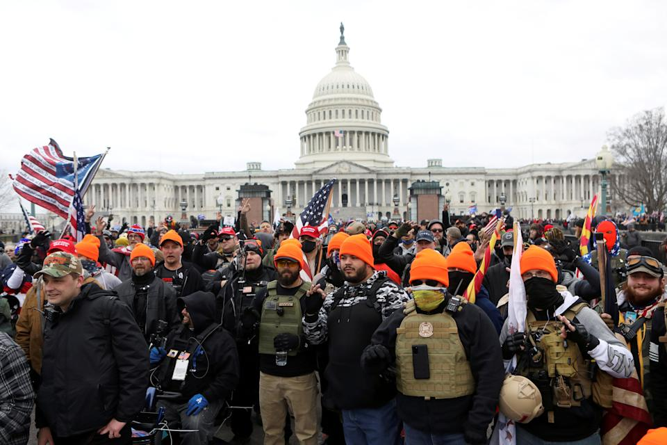 <p>Members of the far-right group Proud Boys gather in front of the US Capitol building</p> (Reuters)