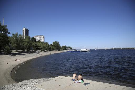 In this Sunday, June 17, 2018 photo, people enjoy a sunny day next to Volga river in Volgograd, Russia. Nearly 60 years since it changed its name to Volgograd, the Russian city once called Stalingrad and its bloody history loom large even in the midst of the fun and football of the World Cup. (AP Photo/Thanassis Stavrakis)