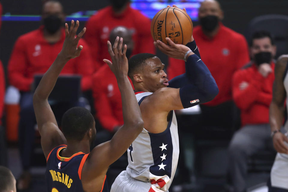 Washington Wizards guard Russell Westbrook shoots next to Golden State Warriors forward Andrew Wiggins during the first half of an NBA basketball game in San Francisco, Friday, April 9, 2021. (AP Photo/Jed Jacobsohn)