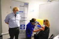FILE - In this June 21, 2021, file photo, Britain's Prime Minister Boris Johnson, left watches as a woman receive her COVID-19 vaccine, as he visits a vaccination center at the StoneX Stadium, home of the rugby club Saracens, in North London. Britain's Conservative government is hoping a combination of relatively high vaccination rates and common-sense behavior will keep a lid on coronavirus infections this fall and winter and avoid the need for restrictive measures. (AP Photo/Alberto Pezzali, Pool, File)