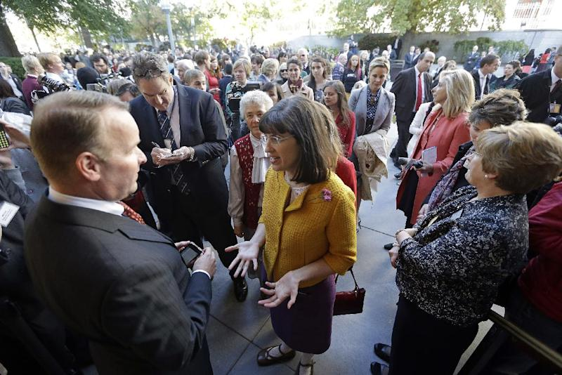 FILE - In this Oct. 5, 2013,file photo, Kate Kelly, center, with a group of about 200 feminist women are denied entrance to an all-male meeting of Mormon priesthood during the Mormon church conference, in Salt Lake City. More than 100,000 Latter-day Saints are expected in Salt Lake City this weekend for the church's biannual general conference. A Mormon's women group pushing the church to allow women in the priesthood plans to demonstrate outside an all-male meeting Saturday. The church has asked them to reconsider, and barred media from going on church property during the demonstration. (AP Photo/Rick Bowmer, File)