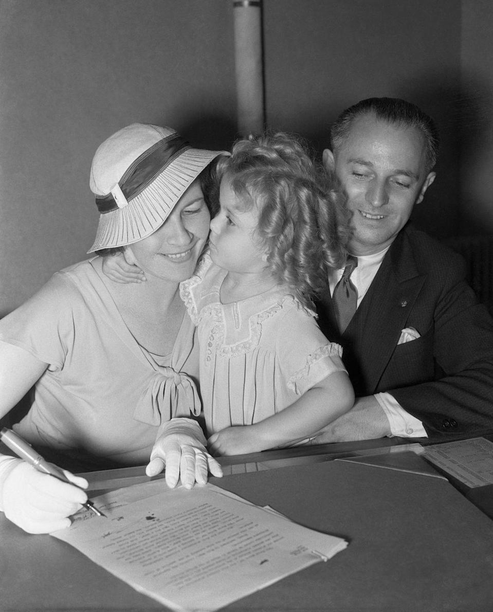 <p>Shirley Temple with her parents as they sign an adjusted, more lucrative contract with Fox Film Corporation. </p>