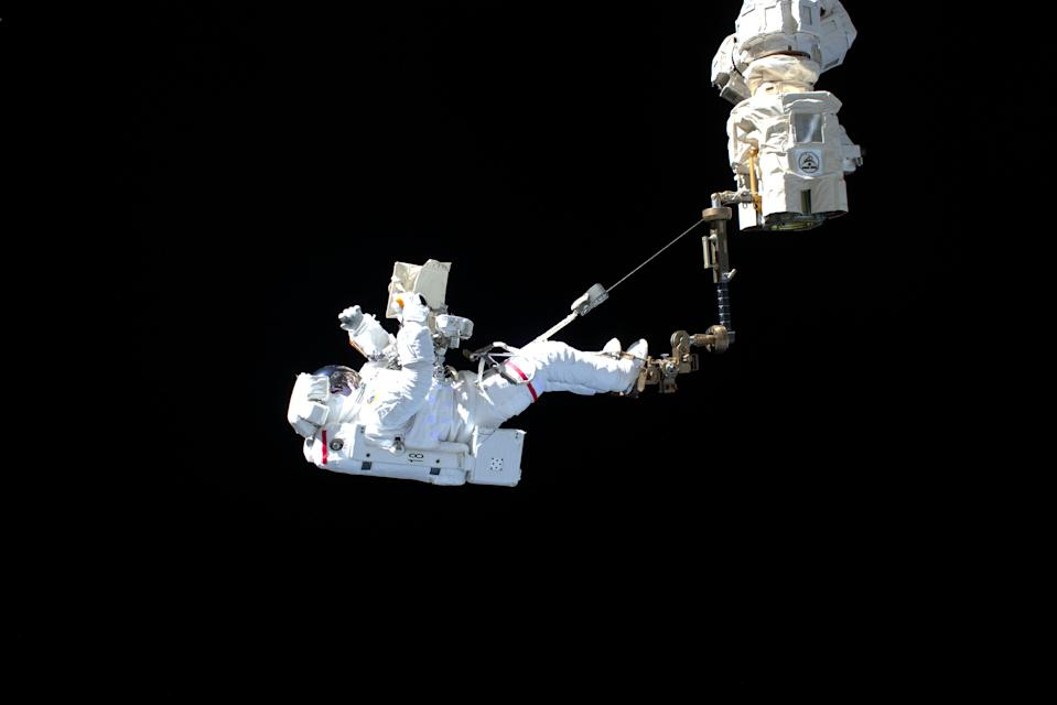 "European Space Agency astronaut Luca Parmitano ""stands"" on the end of the International Space Station's Canadarm2 robotic arm during the first of four spacewalks to repair the Alpha Magnetic Spectrometer experiment together with NASA astronaut Drew Morgan, on Nov. 15, 2019."