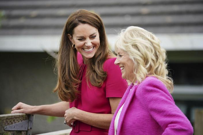 Kate and Jill Biden laugh together as they walk.