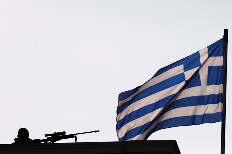 A Police special forces' sniper stands on the rooftop of Zappeion during a Eurogroup meeting, in Athens on Tuesday, April 1, 2014. Finance ministers from the eurozone and the wider European Union are gathering in Athens amid tight security, with Greece hoping for a gesture of support for the release of long-delayed funds from the country's multi-billion-euro bailout. (AP Photo/Kostas Tsironis)